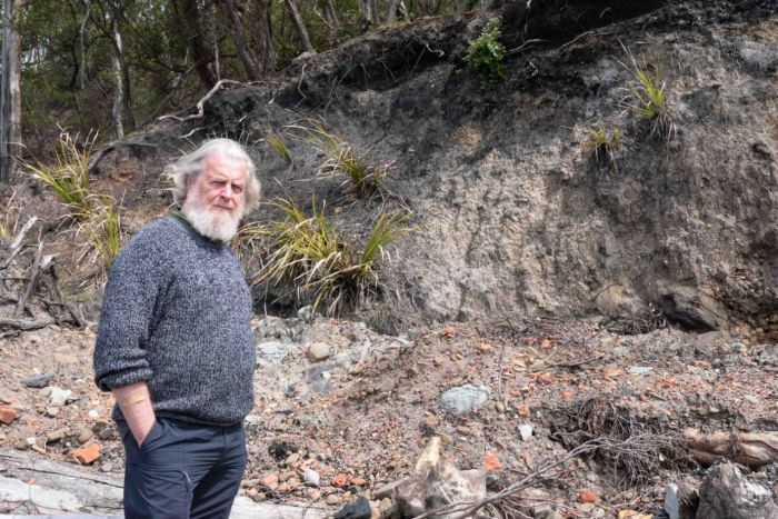 An older man with a white beard stands near an eroded cliff