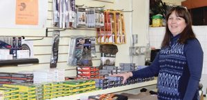 READY, AIM, FIRE — Linda Ballard of Catskill Seasons in Margaretville, stocks new supplies of ammunition in her store, which will be offering holiday hours in the not to distant future. Fishing and hunting licenses are also sold at her Main Street location. CNEws photo by Joan Lawrence-Bauer.