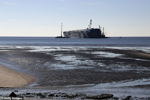 The Golden Ray, a massive cargo ship that overturned on September 8 after departing the Port of Brunswick off the coast of Georgia, about 70 miles, or 112 kilometers, south of Savannah is seen stuck in the sand
