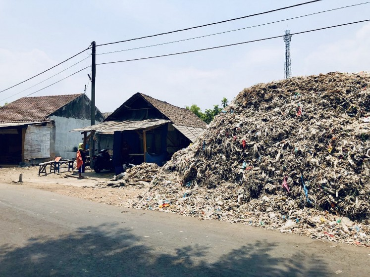 Where's home?: A mound of imported hazardous and contaminated nonhazardous waste is located beside a house in Bangun village, East Java. The village has been inundated by plastic waste imported from Western countries and elsewhere.