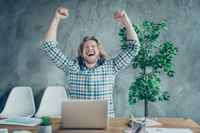 A man sitting at his desk and raising his arms in excitement while looking at his laptop.