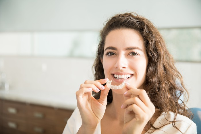 Photo of woman with a clear teeth aligner