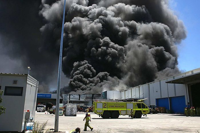 A big plume of smoke above a factory.