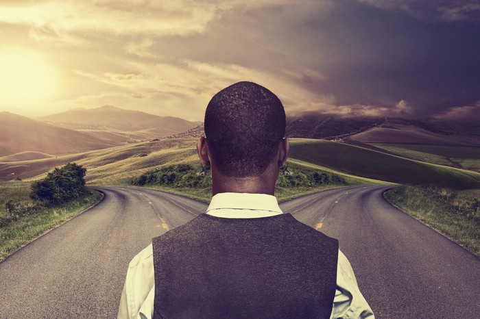 A businessman stands before a fork in the road.
