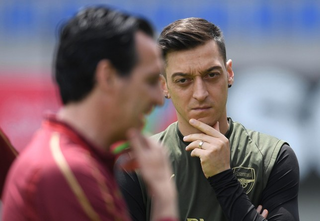 Mesut Ozil watches over Unai Emery during an Arsenal training session