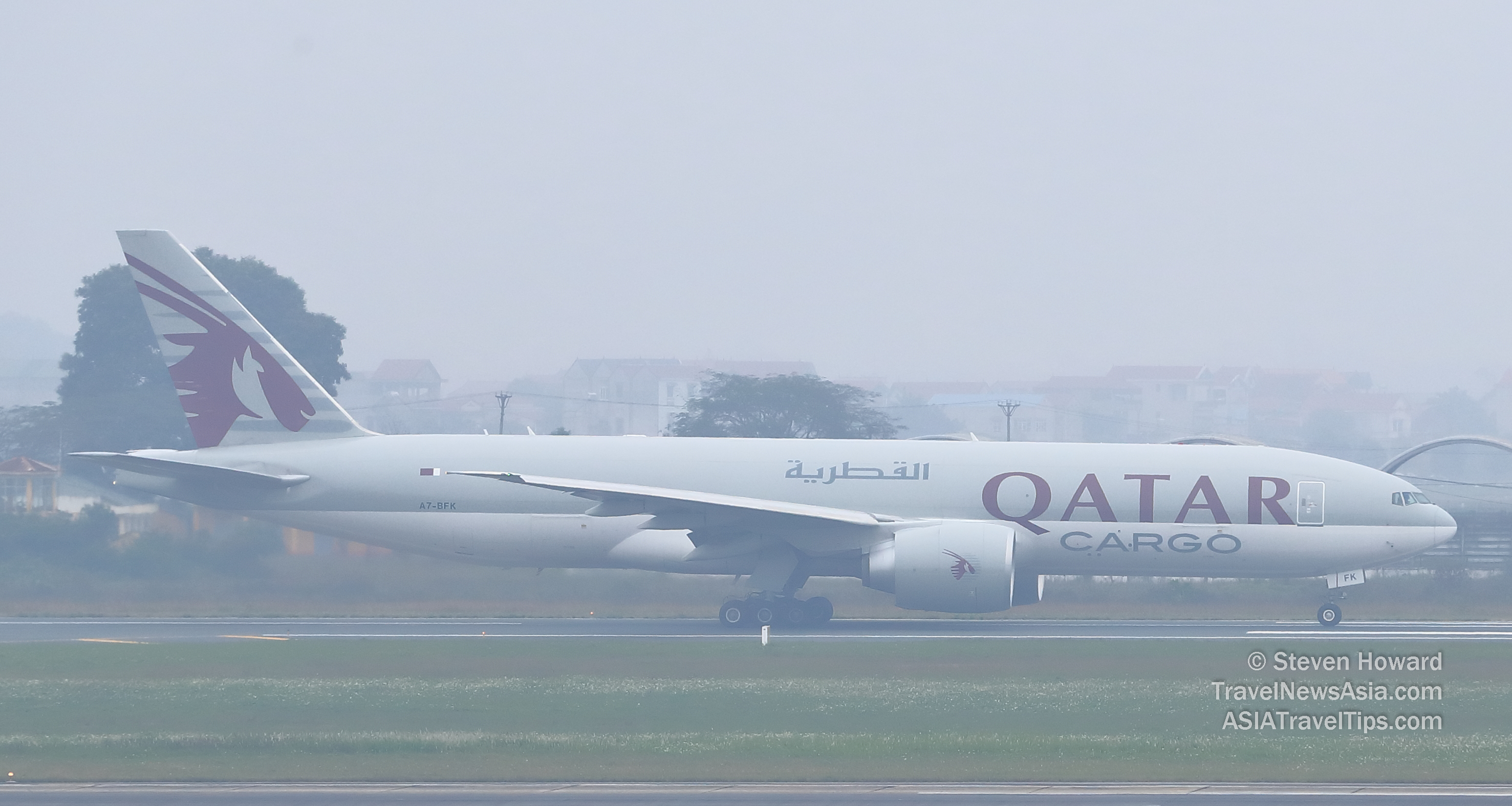 Qatar Airways Cargo Boeing 777F reg: A7-BFK on a very foggy day in Hanoi, Vietnam. Picture by Steven Howard of TravelNewsAsia.com Click to enlarge.