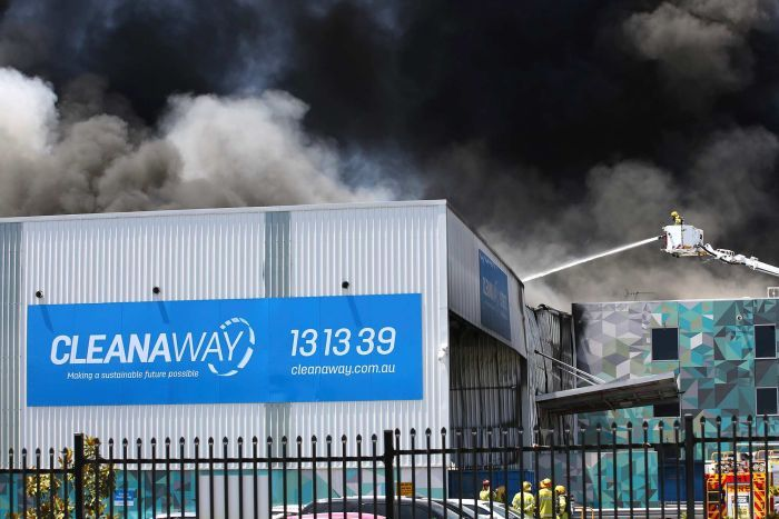 Black smoke fills the sky above a Cleanaway warehouse as a firefighter in a fire truck basket sprays water on the building.