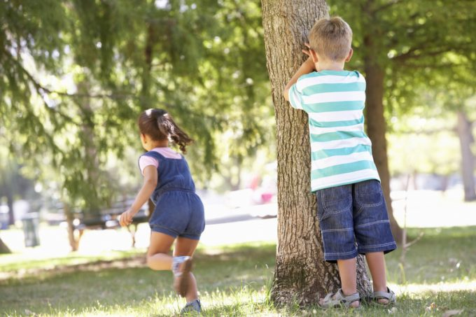 Two Children Playing Hide And Seek In Park