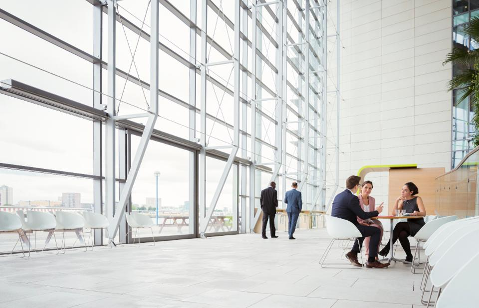 Business people discussing plans in modern lobby