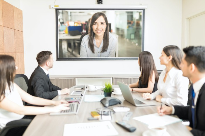 A woman video chatting with a room of business people