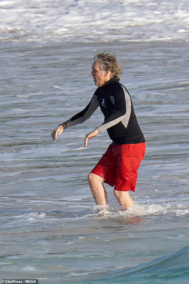 Living it up: After his brief dip in the ocean, Paul went back onto dry land
