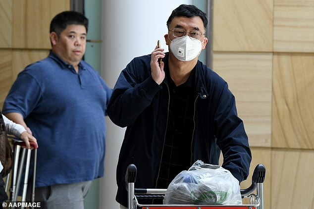 A passenger wearing a protective mask (pictured) is seen at Sydney Airport on Thursday, as a man in Melbourne is confirmed as the first Australian case of coronavirus