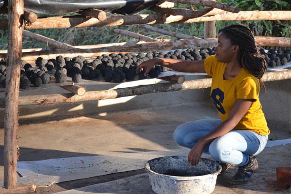 Namutebi organising briquettes at her