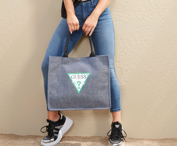 A female model wearing Guess? Jeans holds a Guess? shopping bag