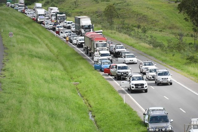A truck rollover has caused traffic to back up for kilometres along the Cunningham Hwy.