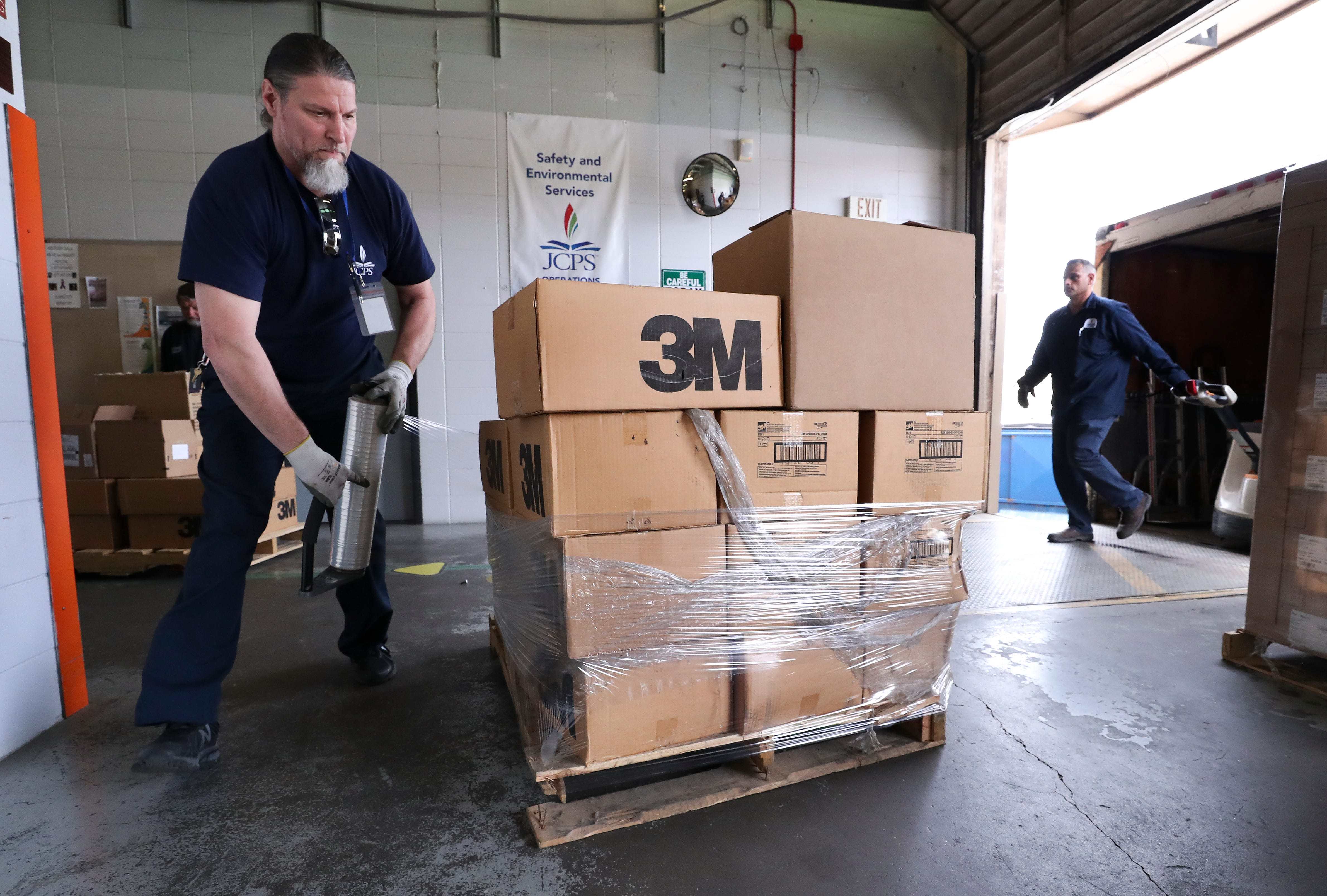 Layman Leasor, a JCPS employee, wraps boxes of personal protective equipment in plastic on a shipping dock at the Young Building on Crittenden Drive in Louisville, Ky. on Mar. 26, 2020.  The school system is donating 40,000 items, including masks and gloves to the Louisville Metro Public Health Department to assist in their efforts to control the spread of the coronavirus outbreak.