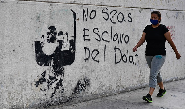 """A woman wearing a face mask walks past graffiti, translated as """"don't be a slave of the dollar"""", in Caracas, Venezuela."""