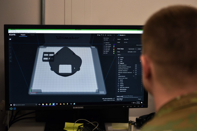 U.S. Air Force Tech. Sgt. Tracy Gibbs, 312th Training Squadron Special Instruments Training course graduate, prepares a 3D printed N95 face mask to be printed through modeling software.