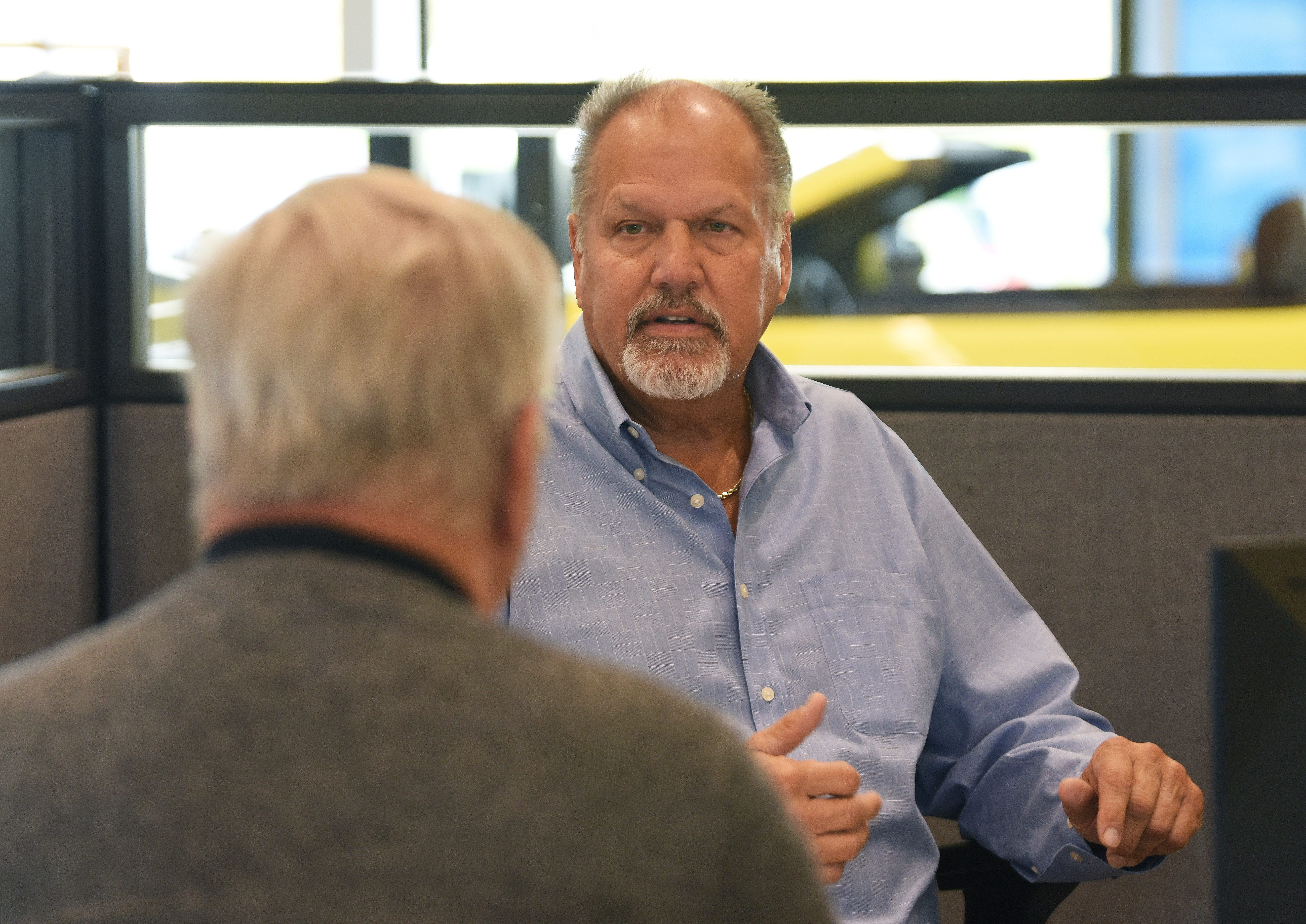 Walt Tutak, right, of Matthews Hargreaves Chevrolet, talks with customer Brian Scraggs. Tutak began to see an inventory crunch easein September, and expects the dealership to sell more vehicles than it did a year ago, despite the pandemic.
