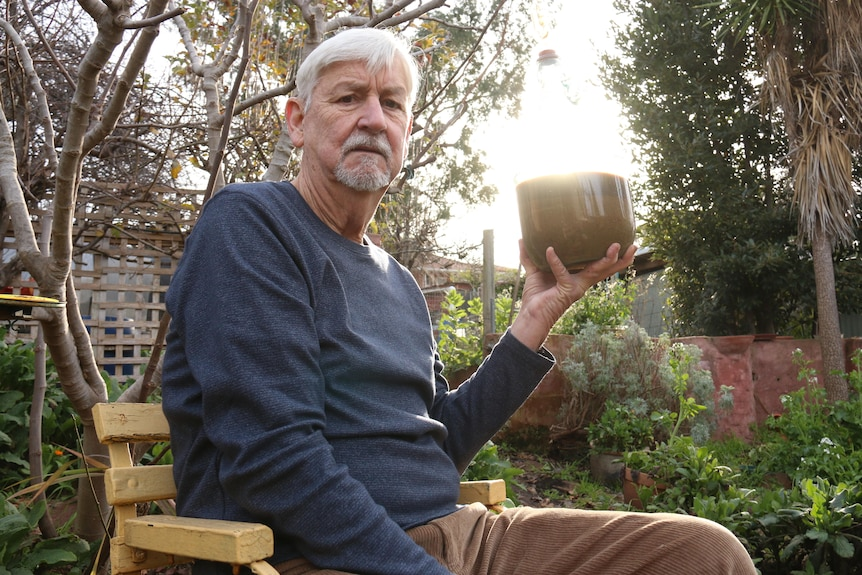 Gerry sits and holds a bottle of brown liquid, outside in his garden.